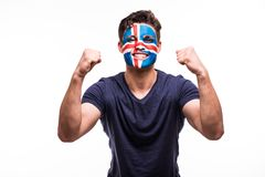 Happy victory scream man fan support Iceland national team with painted face isolated on white background. Happy victory scream woman fan support Iceland royalty free stock photography
