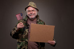 Happy Vietnam Veteran holding a cardboard piece and American fla Royalty Free Stock Images