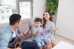 Happy Vietnamese family teaching his son how to play the guitar.  Royalty Free Stock Images