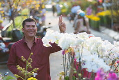 Happy Vietnamese man buying orchids Royalty Free Stock Photography