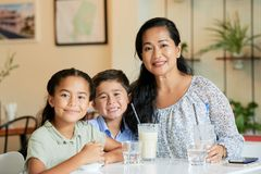 Cheerful mother and kids in caf stock photos