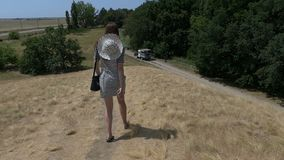 Young woman in a striped dress goes to a truck in slo-mo. A happy view of a young woman in a striped dress who smiles and goes to a small truck on a country road stock video