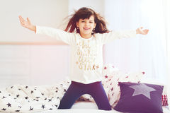Happy vigorous young girl wakes up in the morning sun light, singing in bedroom Royalty Free Stock Images