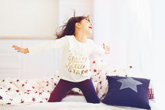 Happy vigorous young girl wakes up in the morning sun light, singing in bedroom Royalty Free Stock Image