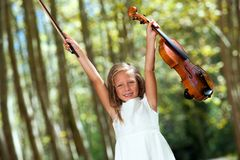 Happy violinist raising violin outdoors. Royalty Free Stock Images