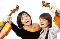 Happy violinists graduates. Two young excited female graduates  holding up violins Stock Images