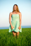 Happy vitality freedom girl stands with her hands. Happy playfull vitality freedom girl stands in green field. Woman lifestyle Stock Photography