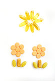 Happy vitamins & healthy growth. Keeping fit - A fun still life image of plants, made with many colorful vitamin and antioxidant tablets and pills. Tablets form Stock Images
