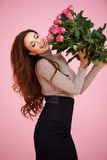 Happy vivacious woman with pink roses. Laughing as she hold them up in the air celebrating her love Royalty Free Stock Photography