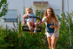 Happy vivacious young mother with her baby son. Playing together outdoors in a playground pushing him on a swing as he laughs happily royalty free stock images