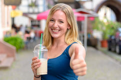 Happy vivacious young woman drinking a takeaway Royalty Free Stock Photography