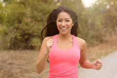 Happy vivacious young woman out running. Along a rural road smiling happily at the camera, close up view in a health and fitness concept Royalty Free Stock Image
