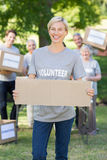Happy volunteer blonde holding blank Stock Photo