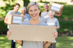 Happy volunteer blonde holding blank. On a sunny day Stock Photos