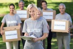 Happy volunteer blonde writing in clipboard Royalty Free Stock Image