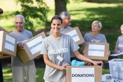 Happy volunteer brunette smiling at the camera Royalty Free Stock Photos