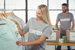 Happy volunteer choosing clothes for donation Stock Image