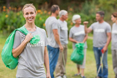 Happy volunteer collecting rubbish. On a sunny day Royalty Free Stock Photography