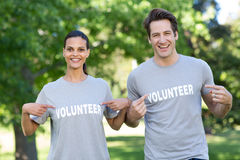 Happy volunteer couple smiling at the camera Stock Images