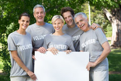 Happy volunteer family holding a blank Stock Photos