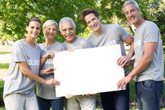 Happy volunteer family holding a blank royalty free stock photos