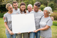 Happy volunteer family holding a blank Royalty Free Stock Photo
