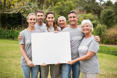 Happy volunteer family holding a blank Royalty Free Stock Images