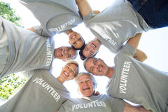 Happy volunteer family looking down at the camera. On a sunny day Royalty Free Stock Images