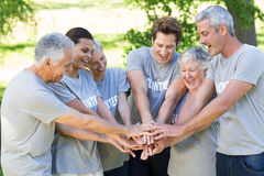 Happy volunteer family putting their hands together. On a sunny day Royalty Free Stock Photo