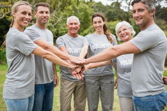 Happy volunteer family putting their hands together. On a sunny day Royalty Free Stock Image