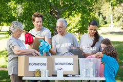 Happy volunteer family separating donations stuffs Royalty Free Stock Images