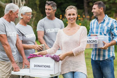 Happy volunteer family separating donations stuffs Stock Image