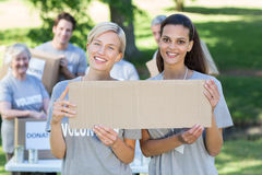 Happy volunteer friends holding blank Royalty Free Stock Photos