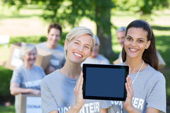 Happy volunteer friends showing tablet pc screen Royalty Free Stock Photo