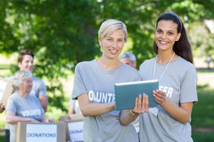 Happy volunteer friends using tablet pc Stock Photo