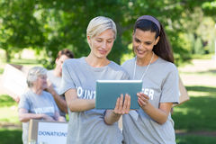 Happy volunteer friends using tablet pc Royalty Free Stock Image