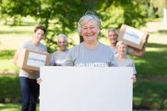 Happy volunteer grandmother holding blank Stock Photo