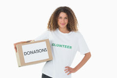 Happy volunteer holding a box of donations with hand on hip Royalty Free Stock Images