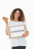 Happy volunteer holding a box of donations and jam jar Stock Photography