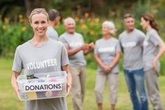 Happy volunteer holding donation box Stock Photo