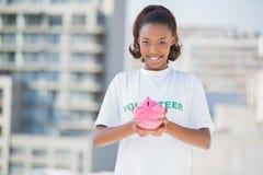 Happy volunteer holding piggy bank Stock Image