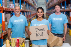 Happy volunteer holding a sign and posing with her team. In a warehouse Royalty Free Stock Images
