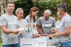 Happy volunteer looking at donation box Stock Image