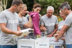Happy volunteer looking at donation box Stock Photo