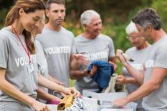 Happy volunteer looking at donation box Stock Photography