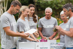Happy volunteer looking at donation box Stock Photography