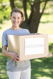 Happy volunteer in the park holding box Stock Image