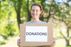 Happy volunteer in the park holding box Royalty Free Stock Photo