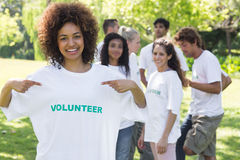 Happy volunteer pointing at tshirt Stock Photos