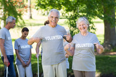 Happy volunteer senior couple smiling at the camera Stock Photos
